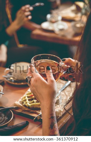 Female hands holding cup of tea in cafe