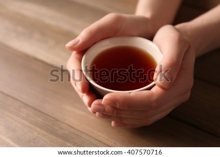 Female hands holding cup of tea on wooden background