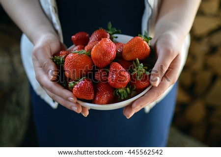 female hands holding handful of strawberries close up