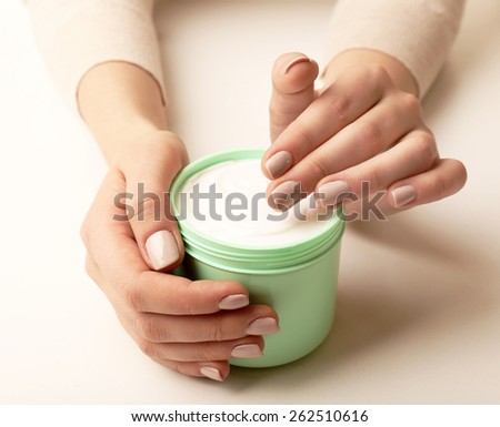 Female hands holding jar of cream isolated on white - stock photo