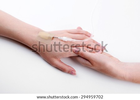 Female hands holding patient hand with dropper needle on bed close-up - stock photo