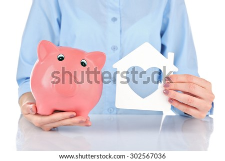 Female hands holding piggy bank and house, closeup - stock photo