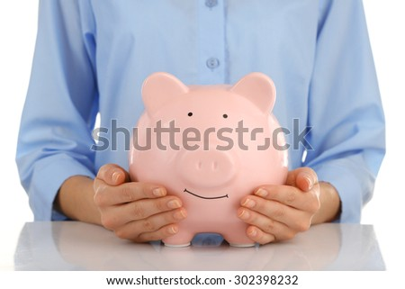Female hands holding pink piggy bank, closeup