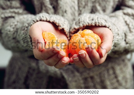 Female hands holding ripe mandarins, close up - stock photo