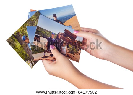 Female hands holding several family vacation photographs - stock photo