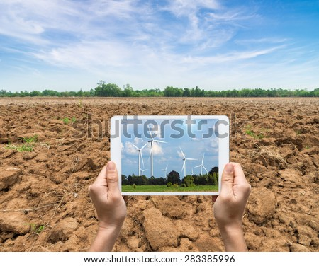 Female hands holding tablet taking pictures Wind turbine power generator on blue sky, industry concept - stock photo