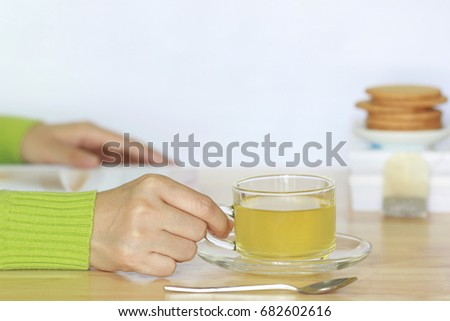 Female hands holding tea cup and open read  on the table