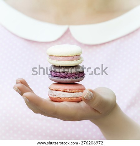 Female hands holding three macaron cakes