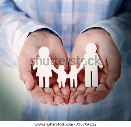 Female hands holding toy family, closeup