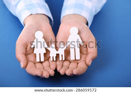 Female hands holding toy family on color background - stock photo