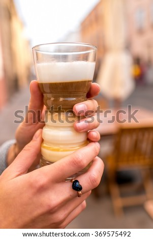 Female hands holding traditioanl canarian coffee barraquito with separated layers in transparent glass on the street cafe background