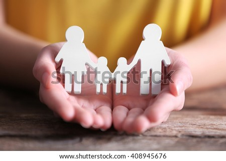 Female hands holding white family figures - stock photo