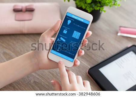 female hands holding white phone with app smart home on the screen on the women table - stock photo