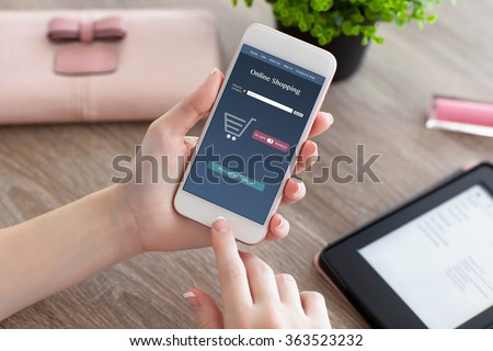 female hands holding white phone with online shopping on the screen and e-rider on the women table - stock photo