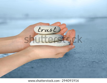 """Female hands holding white stack of pebbles with 'Trust""""' written on the top stone. - stock photo"""