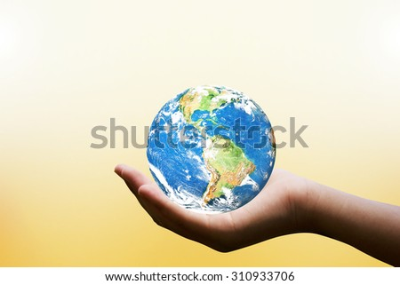 Female hands holding world on blurred sunset background with sun light : Elements of this image furnished by NASA