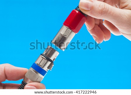 Female hands holding XLR connectors isolated on blue - stock photo