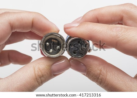 Female hands holding XLR connectors isolated on white - stock photo