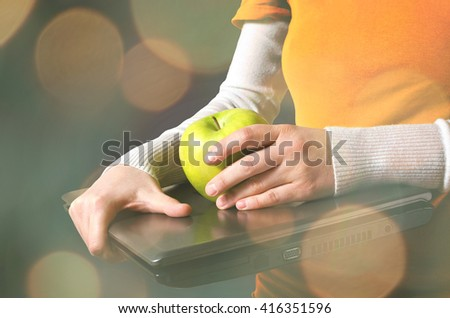 Female hands holds a laptop and a yellow apple with bokeh lights.  - stock photo