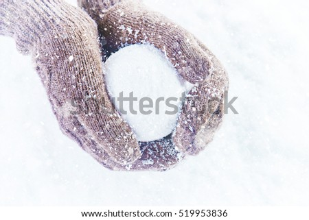 Female hands in knitted mittens with sparkling wonderful snowball on a white snow background. Winter and Christmas concept.