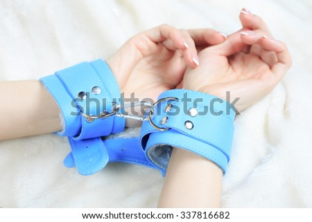 female hands in leather handcuffs. eagerly grabbed the sheets.. sex toys. - stock photo
