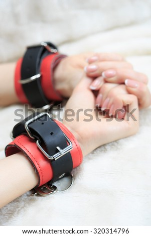 female hands in leather handcuffs. on the background sheet. sex toys. - stock photo