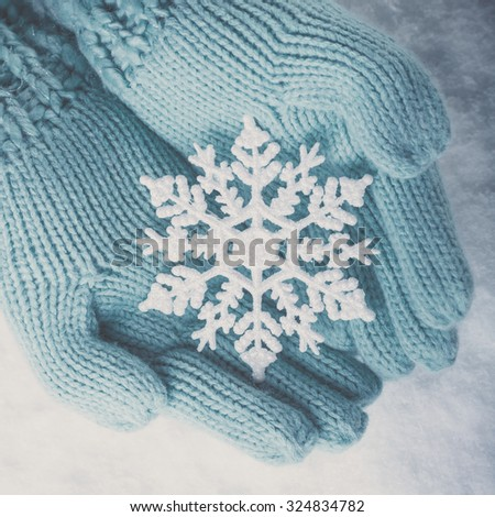 Female hands in light teal knitted mittens with sparkling wonderful snowflake on a white snow background. Winter and Christmas concept. - stock photo