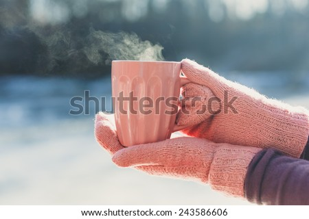 Female hands  in mittens holding cup with hot  tea or coffee. Winter and Christmas time concept - stock photo