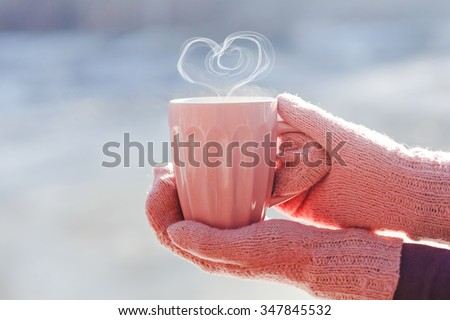 Female hands in mittens holding cup with hot tea or coffee with heart shape close up  - stock photo