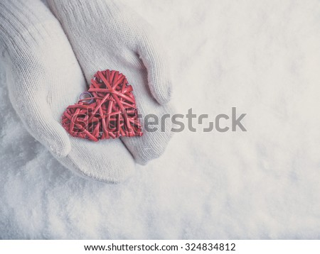 Female hands in white knitted mittens with a entwined vintage romantic red heart on a snow winter background. Love and St. Valentine concept. - stock photo