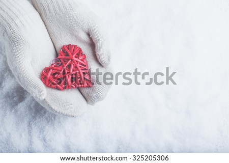 Female hands in white knitted mittens with a entwined vintage romantic red heart on a winter snow background. Love and St. Valentine cozy concept. - stock photo