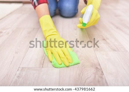 Female hands in yellow gloves wipe the floor rag. - stock photo