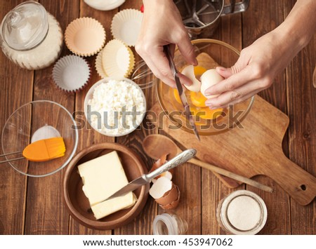 Female hands, ingredients and devices for preparation of cup-cakes on a wooden background. House pastries. Food concept. Flour, eggs, butter, mix for pastries. Top view - stock photo