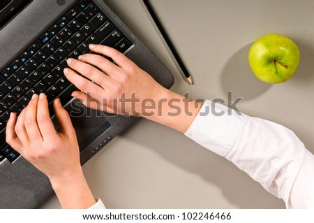 female hands is working on modern laptop, view from above - stock photo