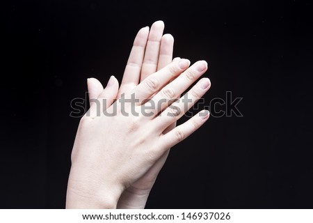 Female hands, isolated on black background, are clapping - stock photo