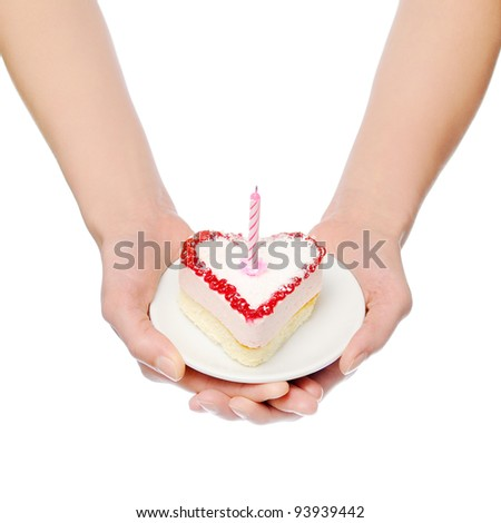 Female hands keep heart-shape cake with candle. Isolated on white - stock photo