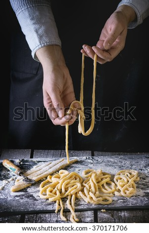 Female hands making pasta pici over wooden kitchen table, powdering by flour. Dark rustic style. See process series - stock photo