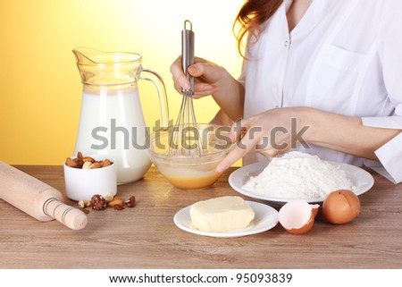 Female hands mixing eggs in bowl on wooden table on yellow background