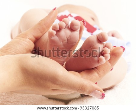 Female hands of young mother holding her baby feet, closeup image with blur baby in background
