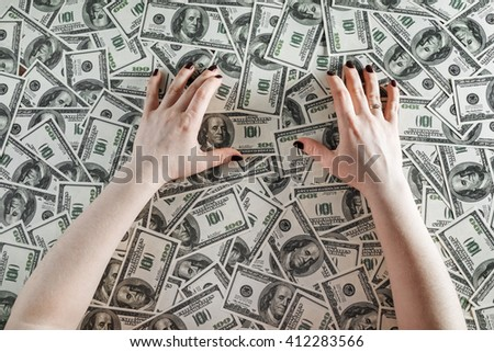 Female hands on a background of money. Hands and money. Many one hundred dollar bills. Fake money. Business concept. Top view. - stock photo