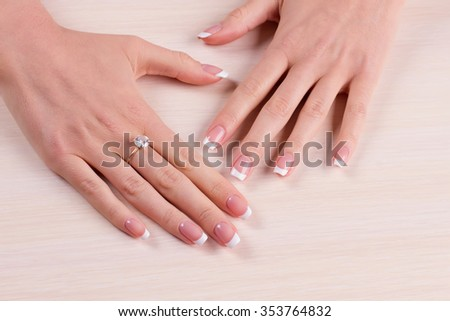 Female hands on a light wooden background. Diamond ring on finger. Gentle french manicure.