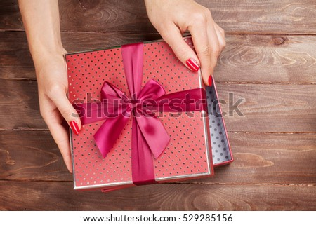 Female hands opening christmas or valentines day gift box above wooden table. Top view