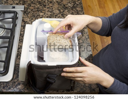 Female hands packing lunch into portable bag while in the kitchen on stone counter top next to stove - stock photo