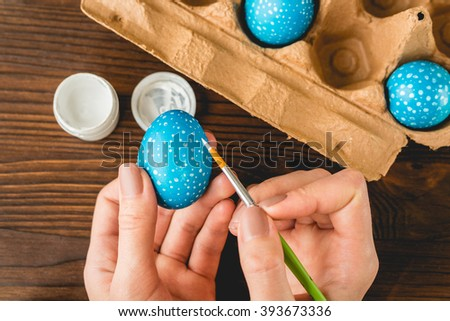 Female hands painted blue Easter eggs with a brush, top view - stock photo