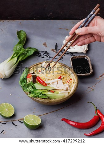 Female hands picking up ingredient from Japanese ramen soup with tofu cheese, noodles, bok choi, smimeji mushrooms, seaweed, chili, and limechopsticks over metal table. Dark rustic style.   - stock photo