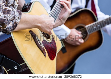 female hands playing acoustic guitar at street concert