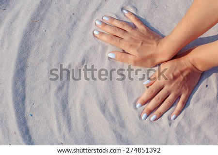 Female hands playing in white sand - stock photo