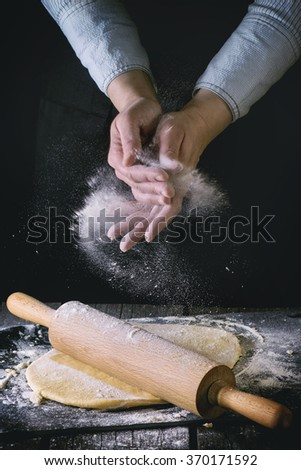 Female hands powdered by flour rolled out dough for pasta with wooden rolling pin over wooden kitchen table. Dark rustic style. With retro filter effect. See process series - stock photo