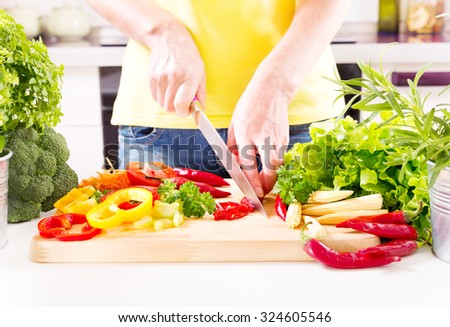 Female hands preparing vegetable salad on wooden board in the kitchen