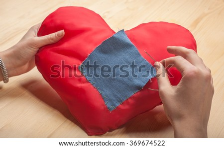 female hands sew a patch on the heart - stock photo